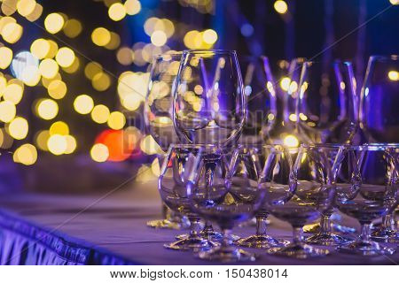 Beautiful row line of different colored alcohol cocktails with mint on a open air party martini vodka with bubblesand others on decorated catering bouquet wedding table on open air event in night