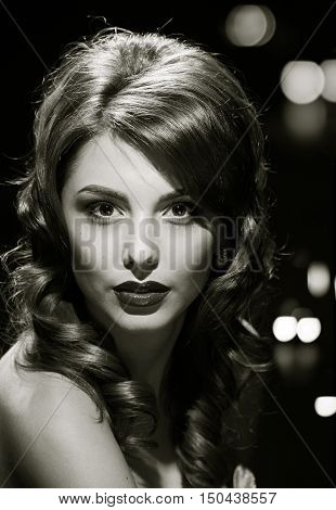 woman studio portrait in hollywood style light with night lights city background. in black and white toning