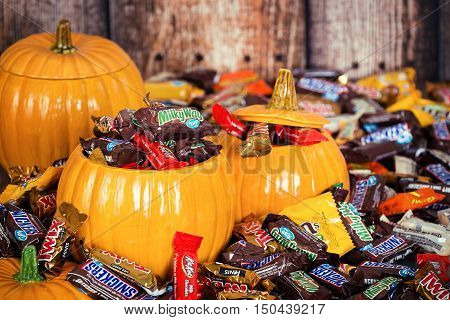 DALLAS TX - OCTOBER 31 2015: Decorative pumpkins filled with assorted Halloween chocolate candy made by Mars Incorporated and the Hershey Company.