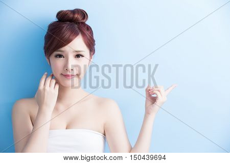 Beauty skin care woman with charming smile and show something to you with health skin and hair isolated on blue background asian beauty
