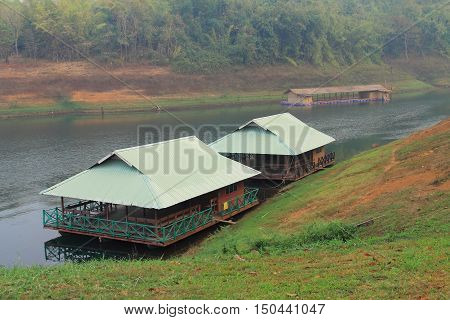 Two green boathouses in the river. Picture of boathouse floating on the river in cloudy day