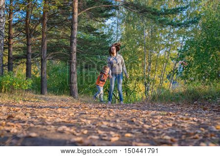 Mother and son running on path in autumn forest. Family at nature autumn bright sunny day fallen yellow leaves underfoot.