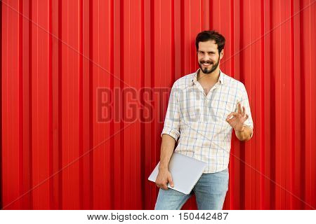 Man Showing Ok Sign With Laptop On Red Background