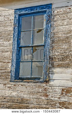 Broken panes and reflections in an old window framed with blue peeling paint and loads of texture