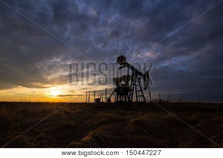 Oil derrick in middle of field under early evening cloudy sky horizontal panorama
