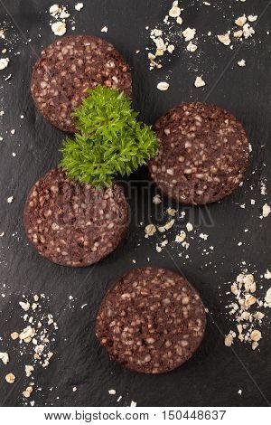 raw irish black pudding with oatmeal and parsley on slate