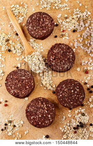 home made irish black pudding with peppercorn oatmeal and coarse salt on wooden board