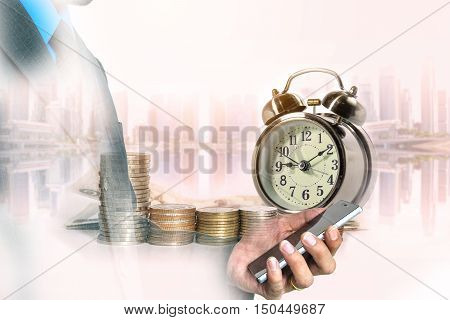 Double exposure of businessman use smart phone with a row of stack money coins and analog clock on the blurred cityscape background concept for business finances and saving money.