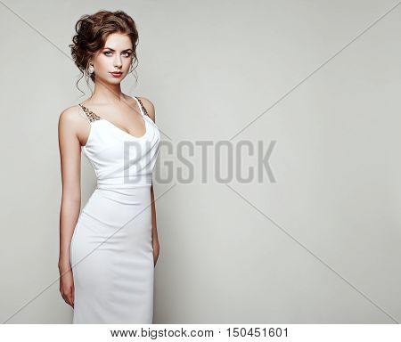 Fashion portrait of beautiful woman in elegant white dress. Girl with elegant hairstyle and jewelry