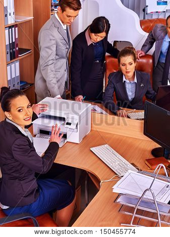 Happy group business people in office. Woman is printing out. Business as usual.