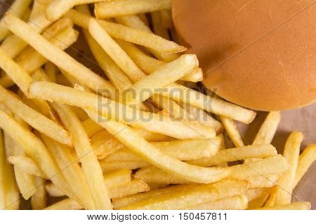 Fried potatoes on brown paper. Red packet in the background. Fastfood