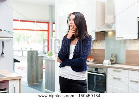 Woman buying domestic kitchen in studio or furniture store