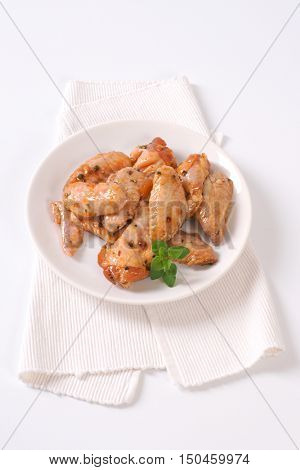plate of marinated chicken wings on white place mat