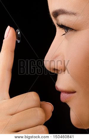 Beauty, vision, eyesight, ophthalmology and people concepts. Closeup profile of Korean or Asian woman putting contact lenses in studio.