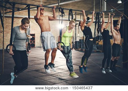 Group of six young and strong male and female adults doing chin ups with bar and straps in cross fit training gym