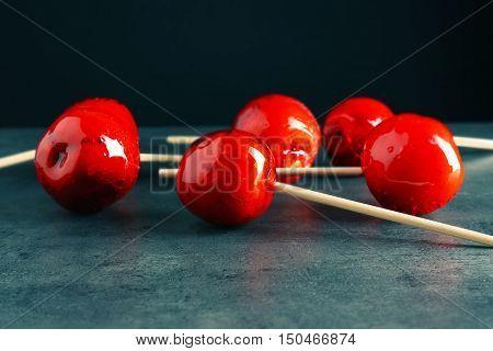Toffee apples on dark background