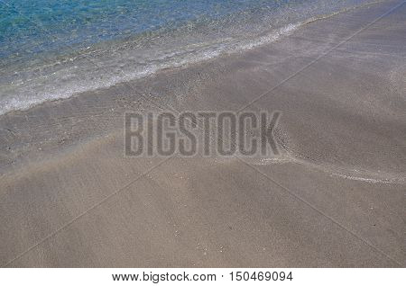 Closeup of the sand and turquoise Indian Ocean waters flowing onto Coogee Beach in Western Australia.