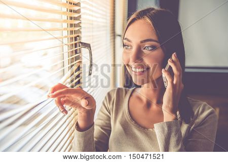 Beautiful young business lady is talking on the mobile phone and smiling while peering through the shutters in office