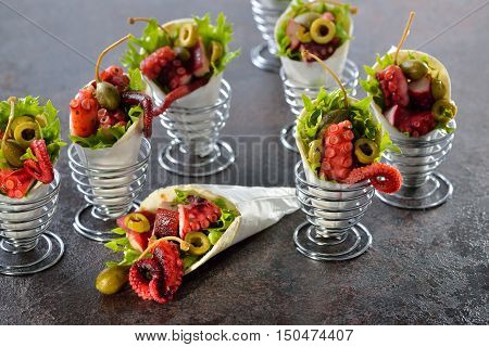Mini tortillas stuffed with octopus salad with olives and capers, served in wire egg cups