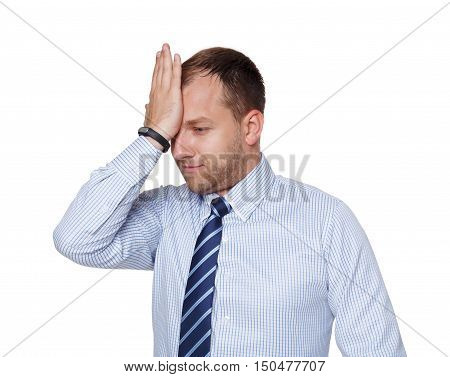 Young tired, depressed and unhappy businessman makes facepalm gesture, isolated on white. Portrait of sad disappointed guy in blue shirt and tie upset about his failure, business problems