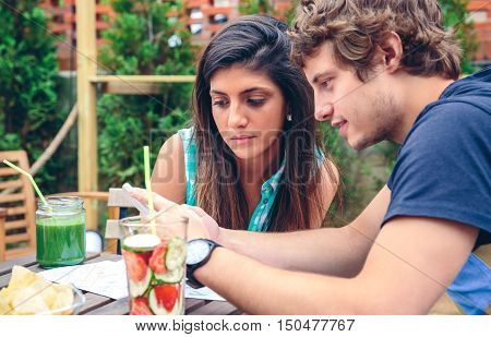 Close up of young couple looking smartphone sitting around of table with healthy drinks in a summer day outdoors