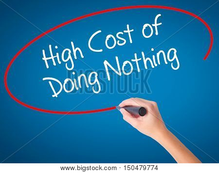Women Hand Writing High Cost Of Doing Nothing With Black Marker On Visual Screen