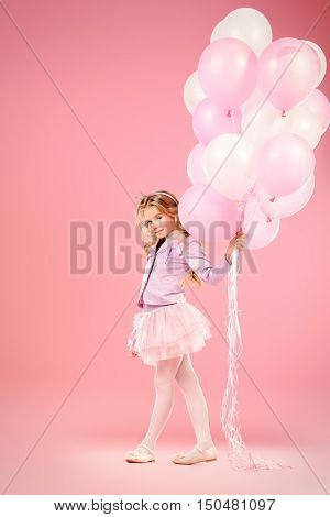 Pretty little girl with beautiful blonde hair alluring with pink balloons over pink background. Little princess with a crown on her head. Kids fashion.