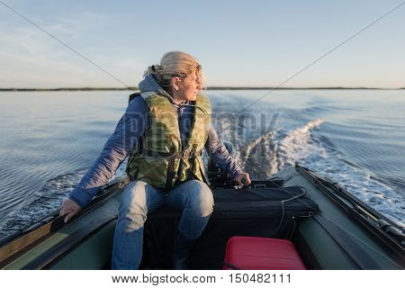 Beautiful woman is operating of boat on the sea