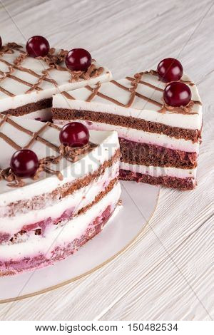 Chocolate cake with mousse decorated with cherries and chocolate. Closeup