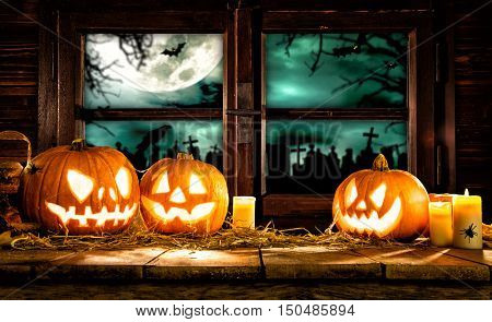 Scary halloween pumpkins on wooden planks, placed in front of window with scary background