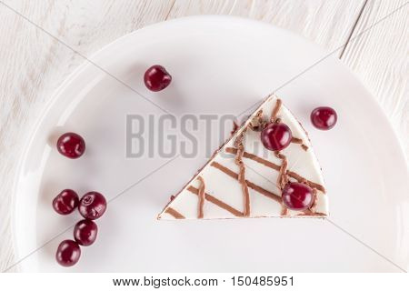 Piece of chocolate cake on plate decorated cherries and chocolate