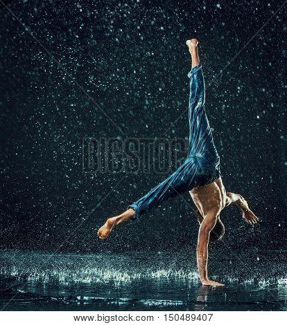 The male break dancer in water on dark background.