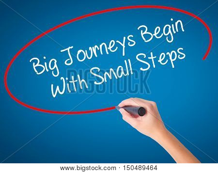 Women Hand Writing Big Journeys Begin With Small Steps  With Black Marker On Visual Screen