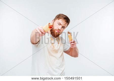 Hungry bearded man in filthy shirt holding two hotdogs isolated on white background
