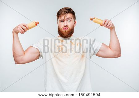 Funny bearded man in filthy shirt holding to hotdogs isolated on white background