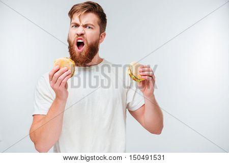 Excited bearded man greedily eating hamburgers isolated on white background