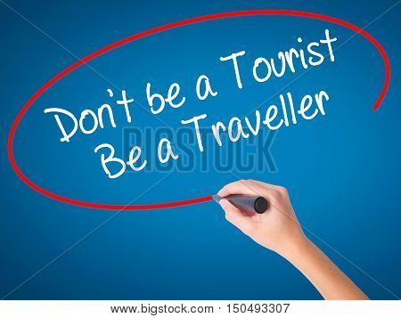 Women Hand Writing Don't Be A Tourist Be A Traveller  With Black Marker On Visual Screen
