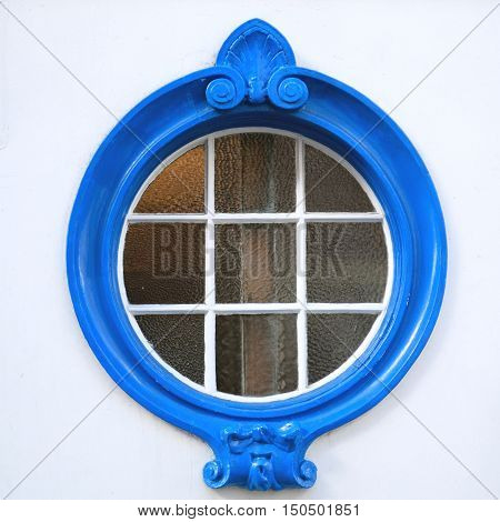Architectural detail of beautifully decorated blue wooden circle window on a building with facade painted in white