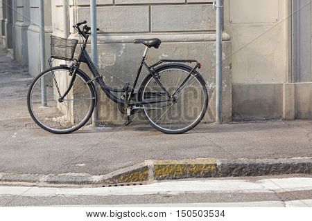 Old styled Bicycle with basket parking near street. Chained black bike in the corner outside the building.