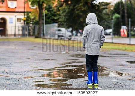 Boy In Rubber Blue Rain Boots Walking In The Rain