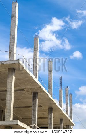 New unfinished monolithic concrete building framework with blue sky in the background. Construction background.