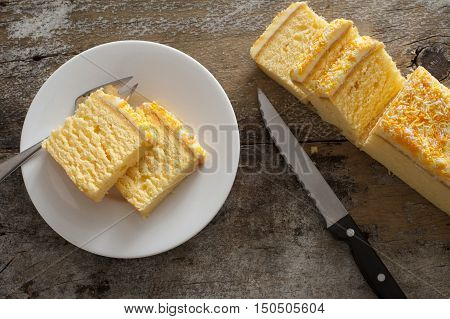 Overhead view of mouth watering yellow cake on round white plate with fork beside knife