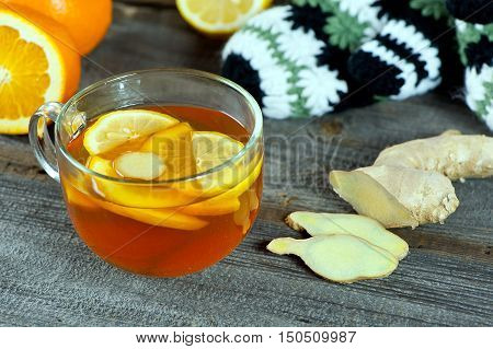 glass cup of warming ginger tea with slices of orange and lemon. Winter woolen gloves and tea container in background.