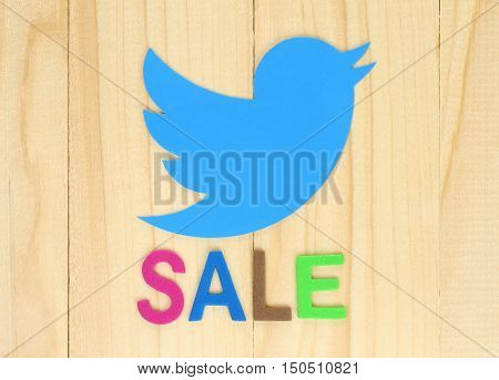 Kiev Ukraine - September 29 2016: Twitter icon printed on paper with color label Sale on wooden background. Twitter soon will be sold