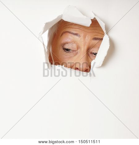 curious mature woman looking through hole. with copy space.