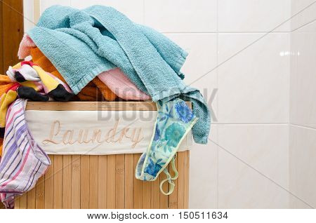 Laundry wood basket with colored towels inside