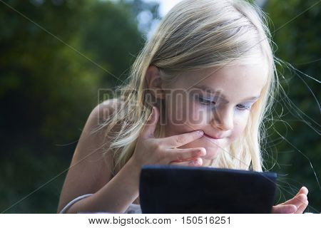 Close up portrait of adorable little child blond girl playing with mommy's make up outside