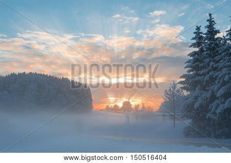 Winter morning snowy tranquil rural scenery with fog over snowbound forest and dawn sunlight rays breaking through clouds
