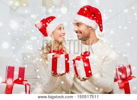 christmas, holidays and people concept - happy couple in santa hats exchanging gifts at home