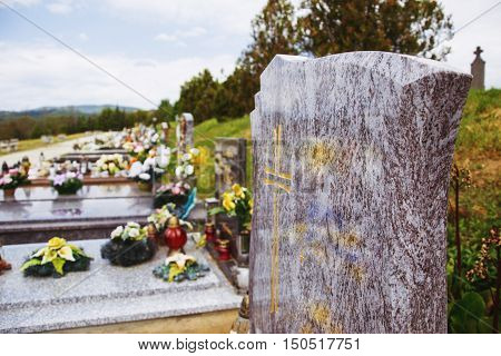 Close up of empty tombstone. Graves, tomb stones and crucifixes on traditional public cemetery. Votive candles lantern and flowers on tomb stones on graveyard in Slovakia